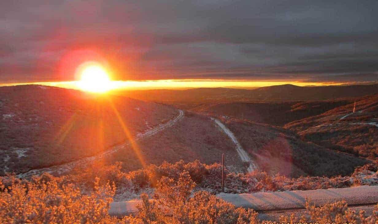 Opgaande zon en een pad door de bergen, als symbool voor de weg die je af kunt leggen tijdens een traject online coaching.