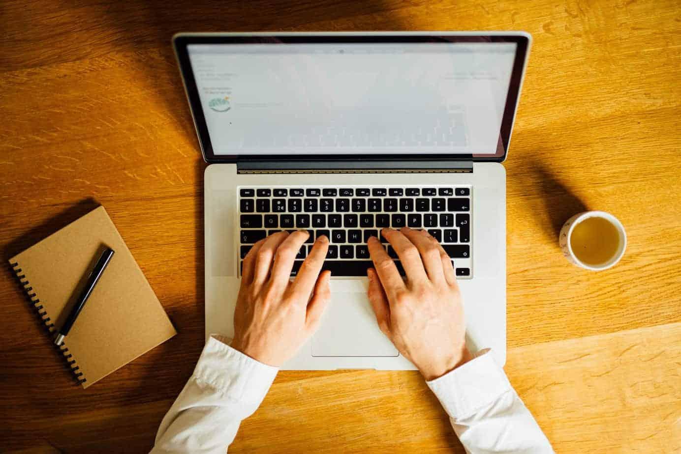 Online coaching vanuit thuis heeft vele voordelen: een openstaande laptop met handen die aan het tikken zijn, op een houten tafel met een notitieboekje en kop thee.