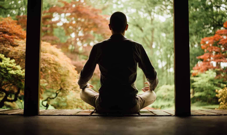 De trainer Marc van Heyningen in meditatiehouding in de Japanse tuin in Clingendeal.