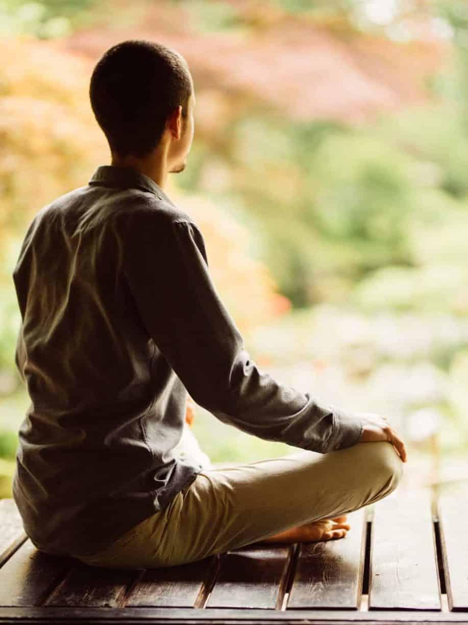 Marc van Heyningen in meditatiehouding op een houten vlonder in de Japanse tuin in Clingendael.