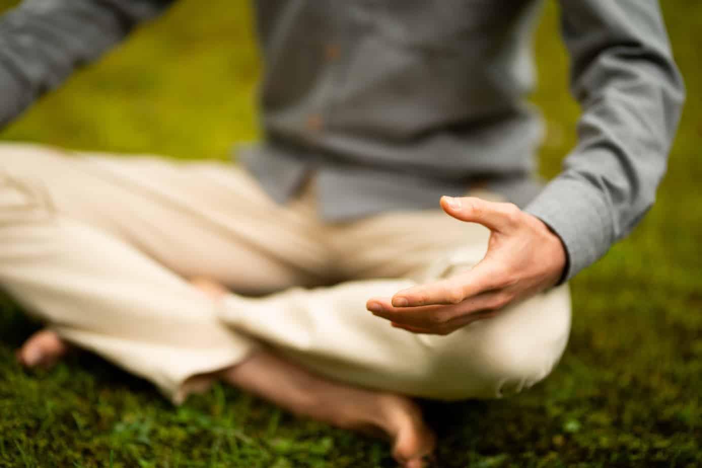 De trainer die de mindfulness online begeleid in meditatiehouding in het gras.