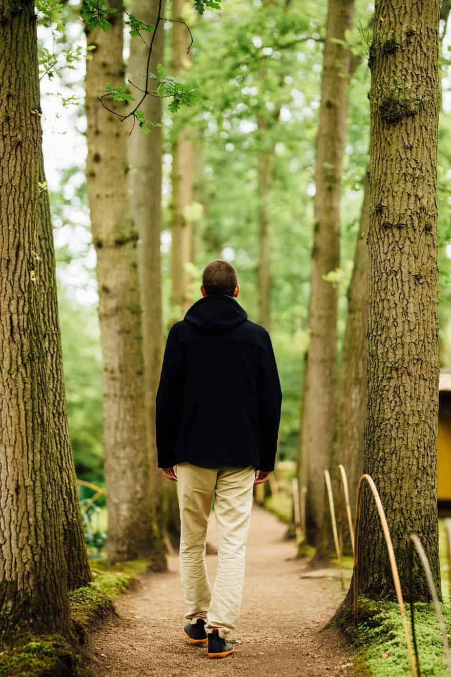 Man alleen lopend in de natuur tussen de bomen door.