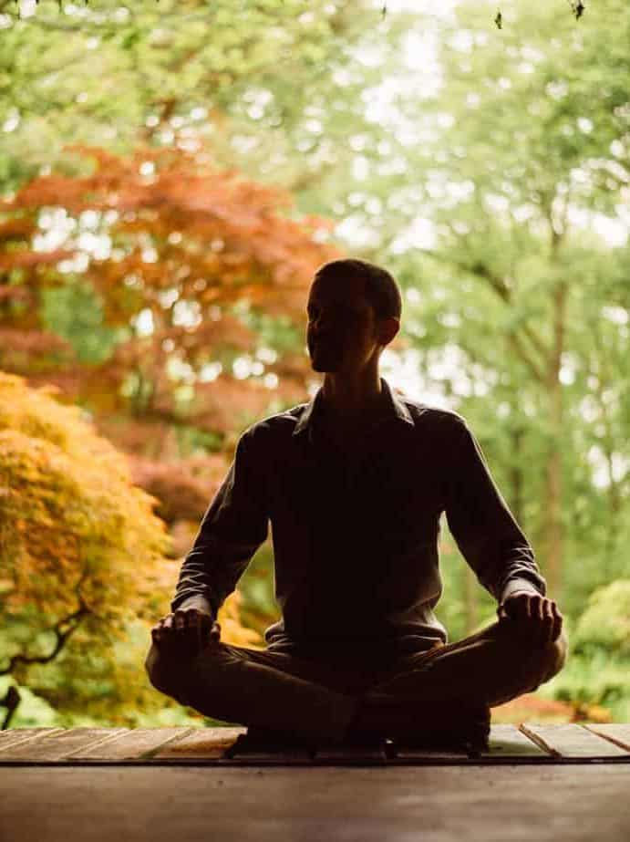 Trainer alleen zittend in meditatiehouding met natuur op de achtergrond: Volg een individuele mindfulnesstraining.