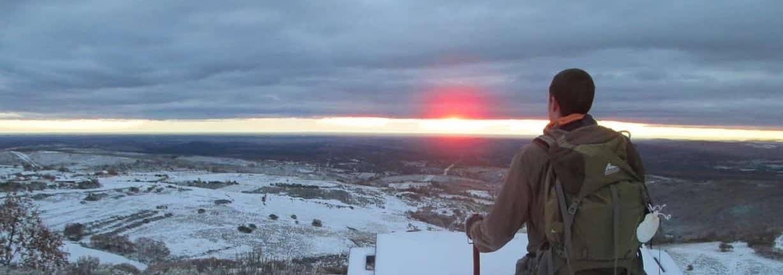 Wandelaar staand op een berg met uitzicht over de horizon. Dat geeft pas rust in je hoofd.