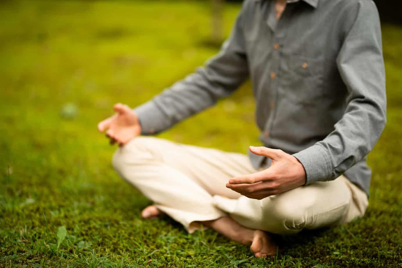 Trainer die Mindfulness geeft in het Westland in meditatiehouding in het gras.