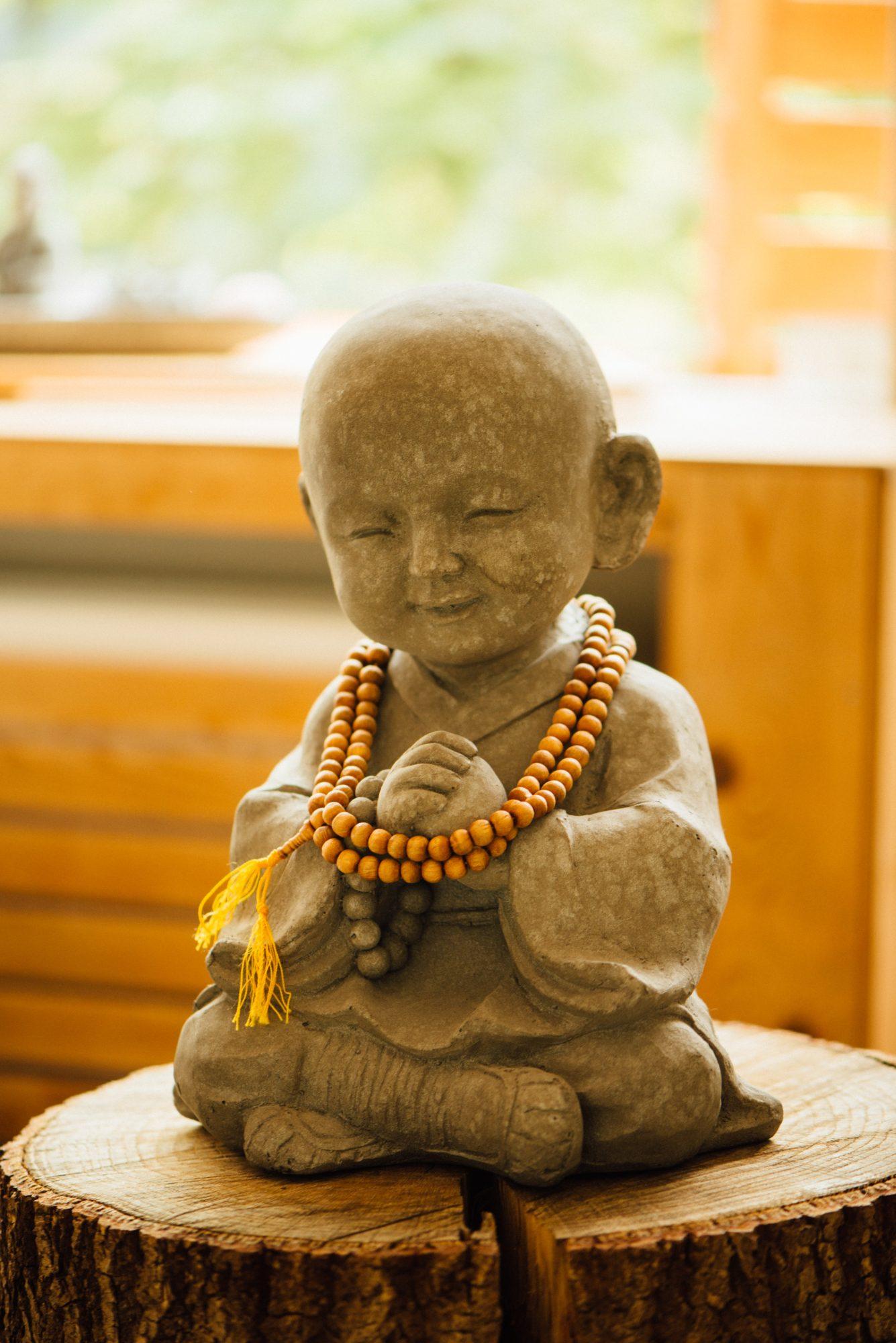 Beeld van een kind als Boeddha, met een glimlach op zijn gezicht.