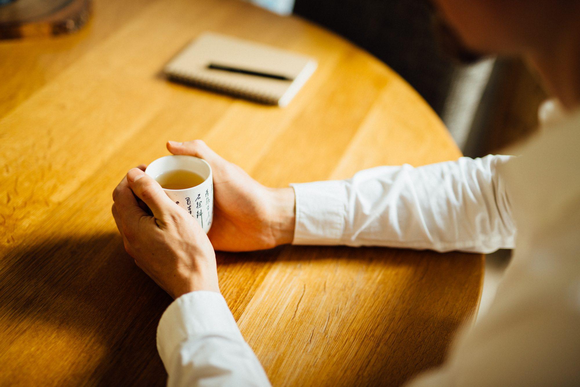 Coach zittend aan een tafel met een kop thee. Een coachingstraject is ook gewoon vanuit je eigen huis mogelijk.
