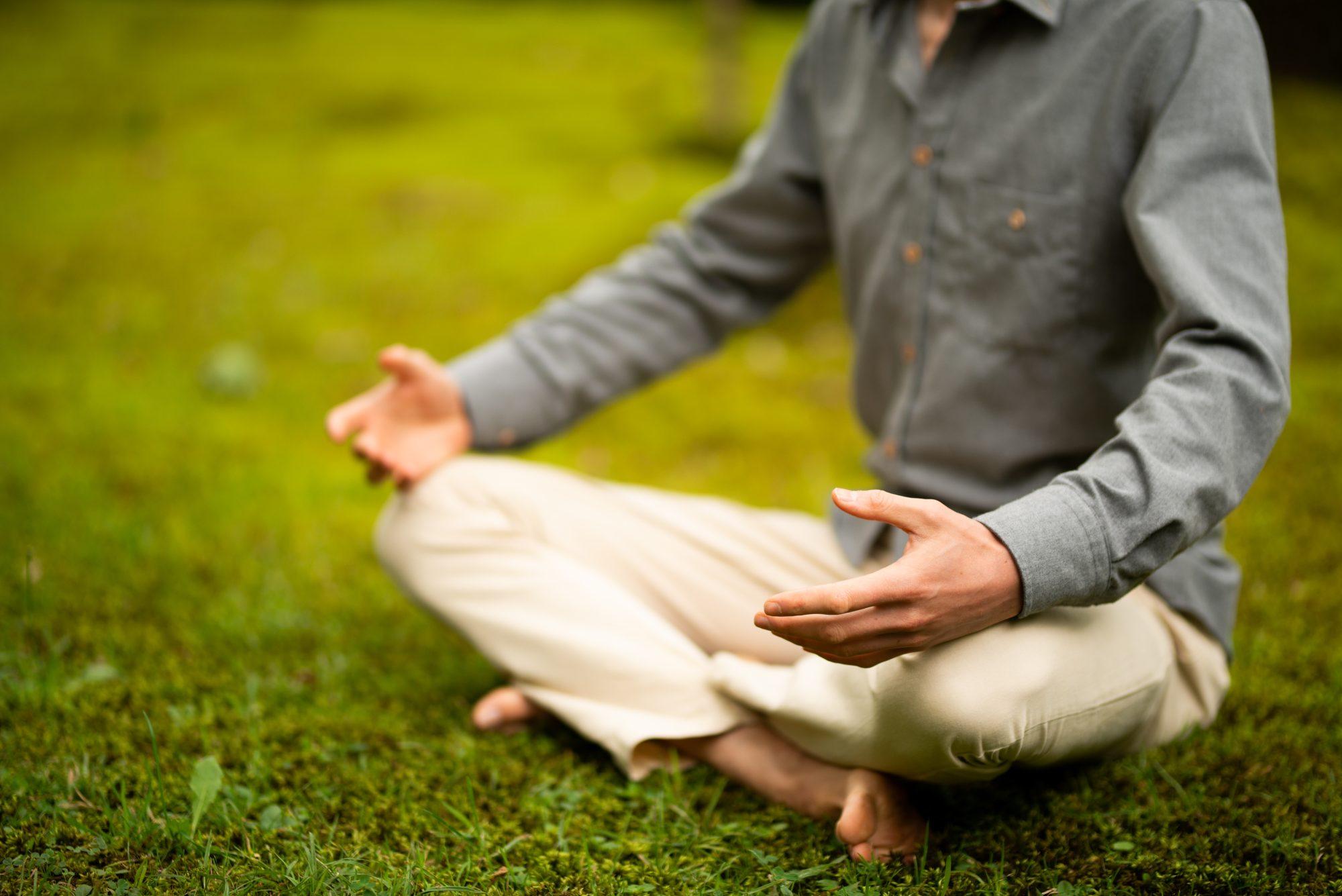 Mindfulness Individueel: Trainer zittend in meditatiehouding in het gras.