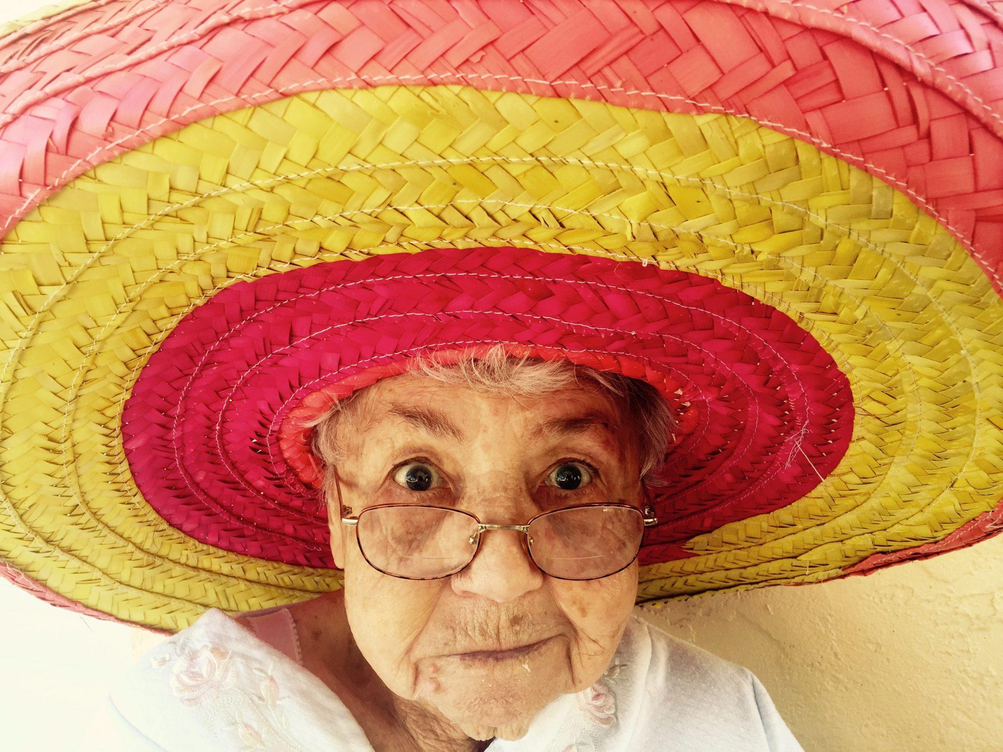 Een oma met een kleurrijke hoed op: lach gewoon eens om je oordelen, meningen en adviezen.
