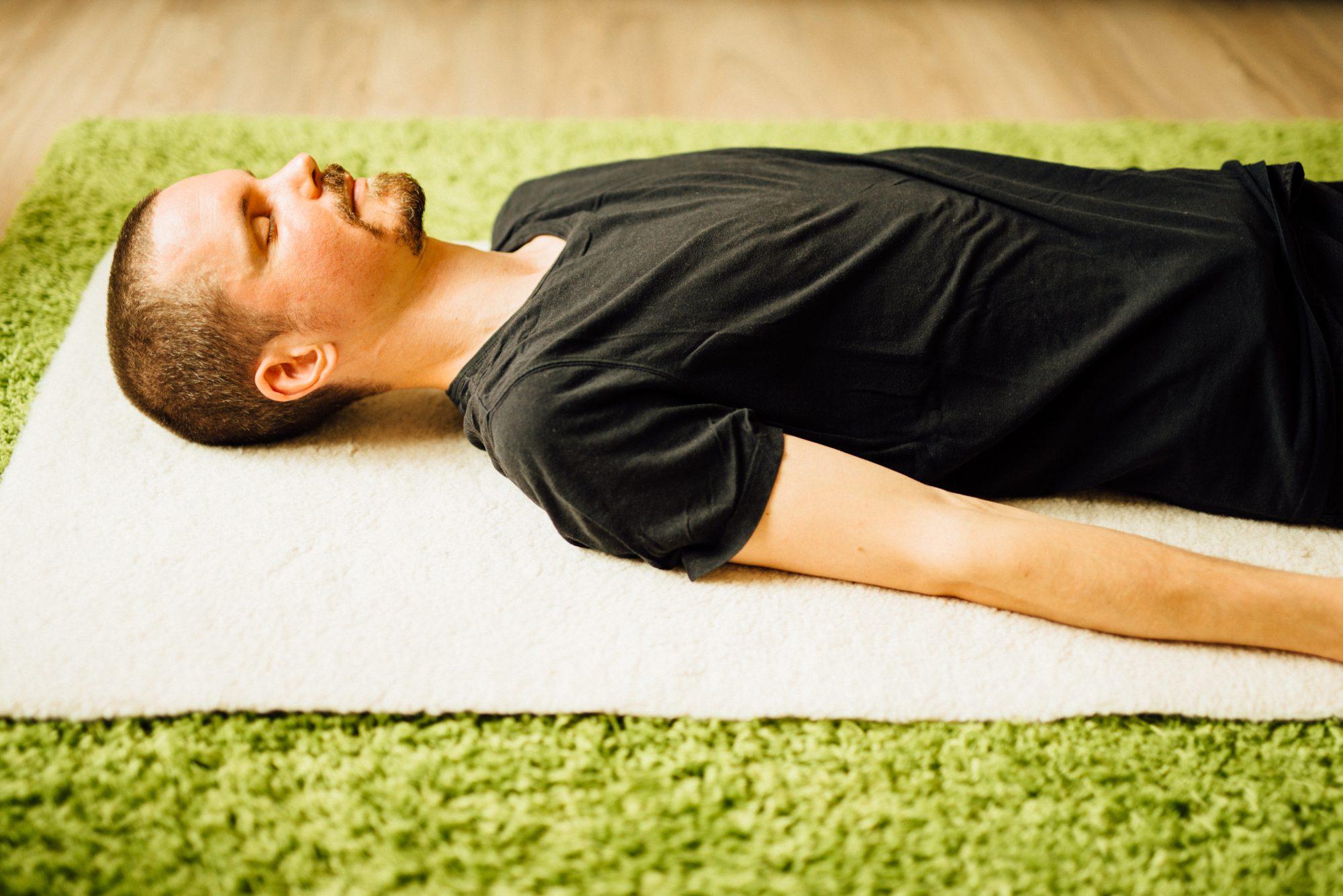 Trainer die Mindfulness in Utrecht geeft ligt ontspannen op de grond tijdens een liggende meditatie.