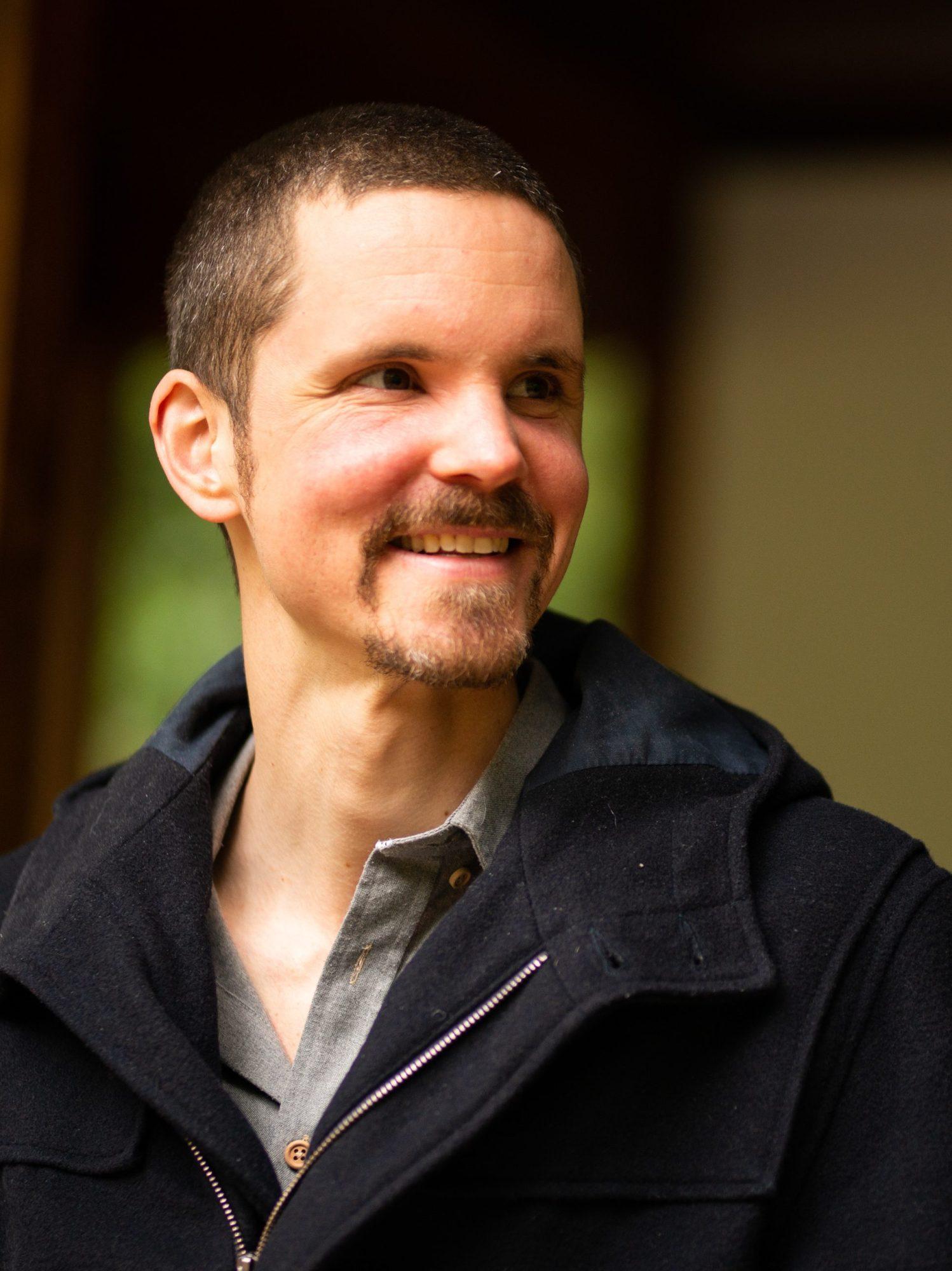 Mindfulnesstrainer Marc van Heyningen die vrolijk lacht.