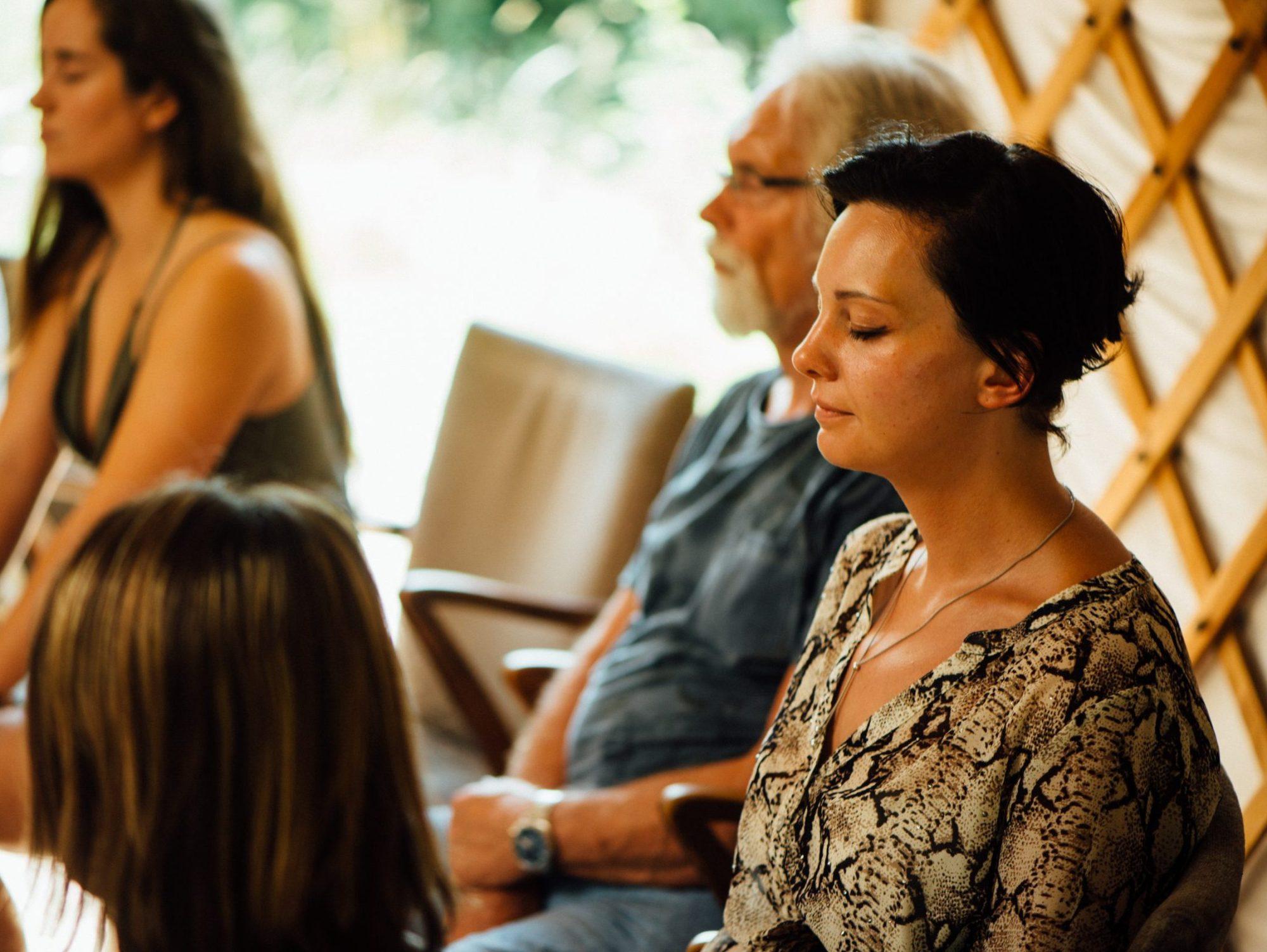 Deelnemers in meditatie tijdens een meditatiegroep.